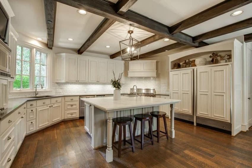 Mediterranean kitchen with white cabinets wood floor and exposed beam ceiling