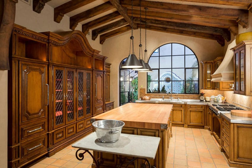 Mediterranean kitchen with wood counter island tile floors beamed ceiling