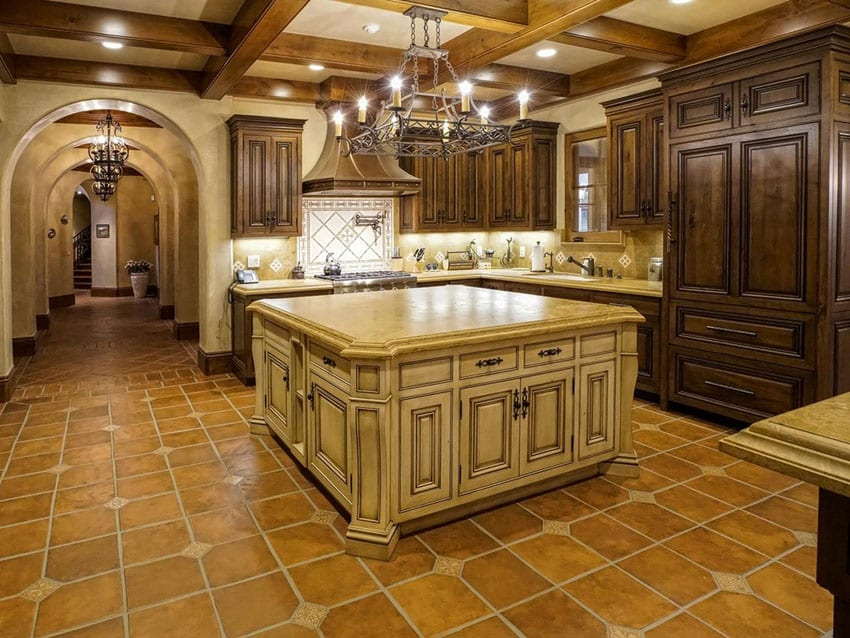 Mediterranean style kitchen with crema cappuccino marble countertop and adobe tile floors