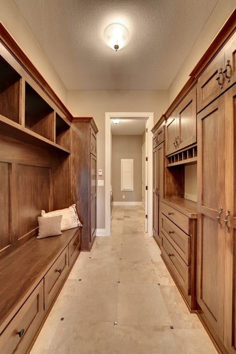 Narrow walk in closet with wood cabinets and marble floor tile