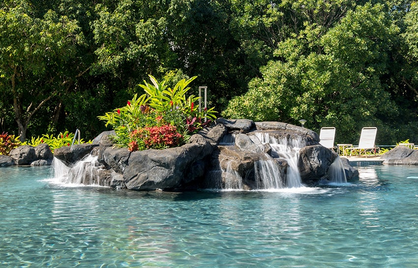 Hot tropical swimming pool at resort with waterfall feature and reclining chairs on the patio with turquiose water