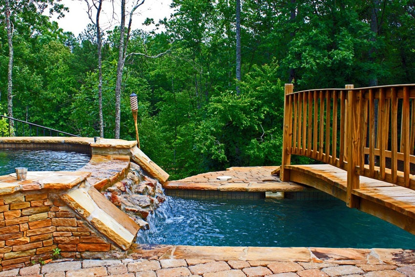 Natural looking rock waterfall attached to swimming pool