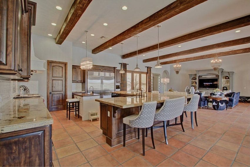 Open concept kitchen with terra cotta tile flooring beam ceiling