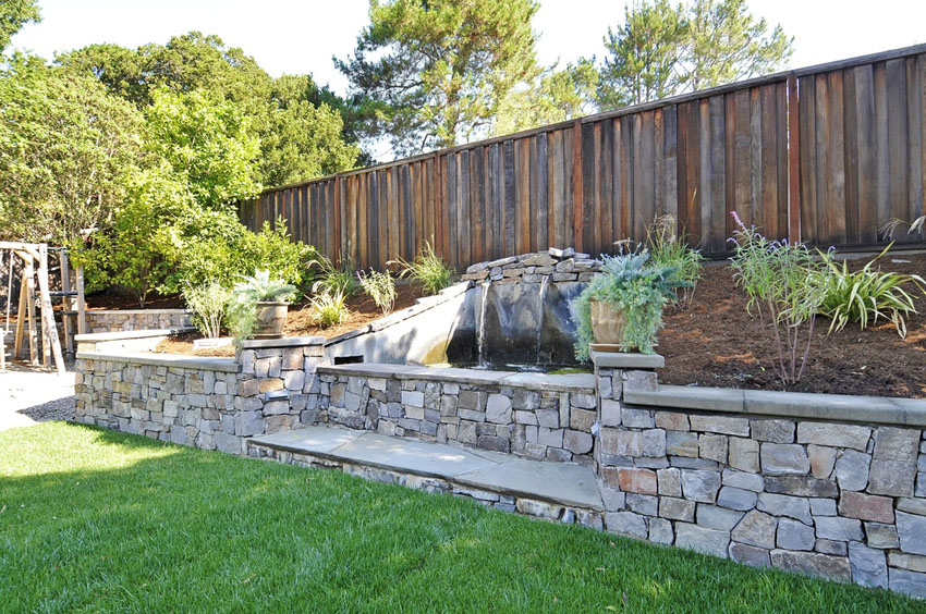 Raised backyard waterfall over grass