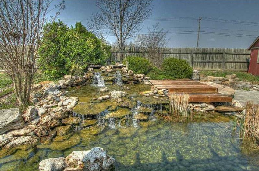 Rock waterfall and pond next to wood deck