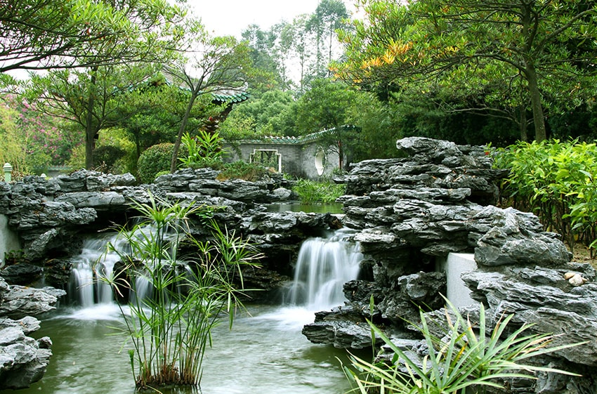 Chinese garden with flowing waterfalls pver natural looking stone formations