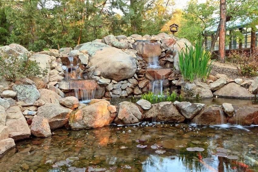 Rustic rock waterfall in backyard
