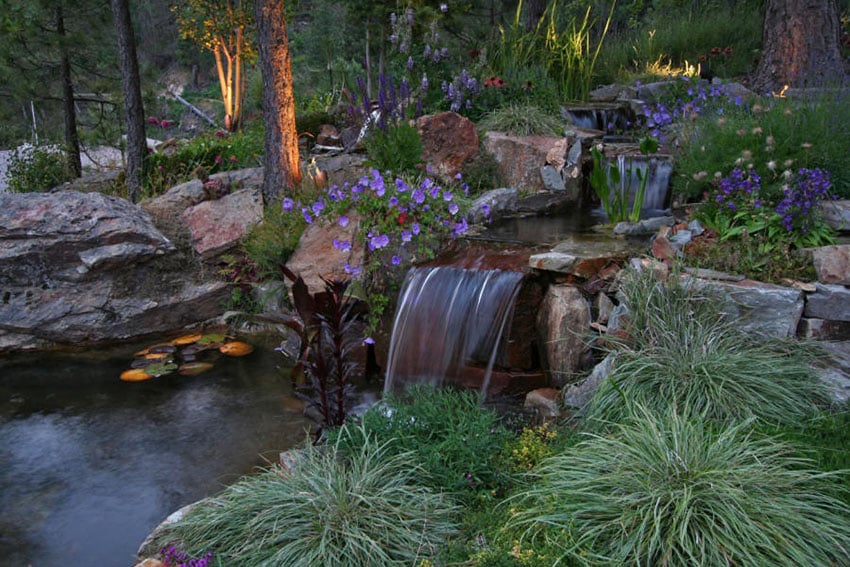 Small creek water feature with waterfalls in to pond