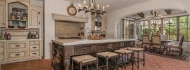 spanish-style-kitchen-with-off-white-base-cabinets-dark-island-terra-cotta-floors