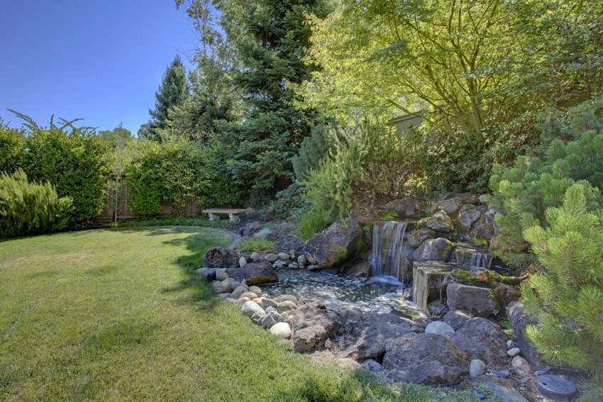 Stone waterfall and pond next to backyard lawn