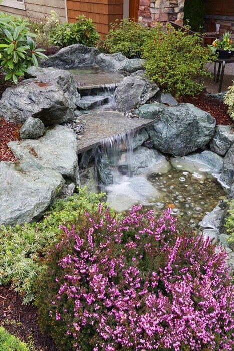 Two-tiered stone waterfall in backyard garden