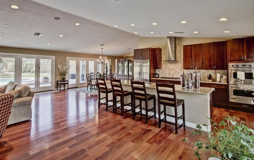 Traditional kitchen with open layout with hardwood floors and long rectangular dining island