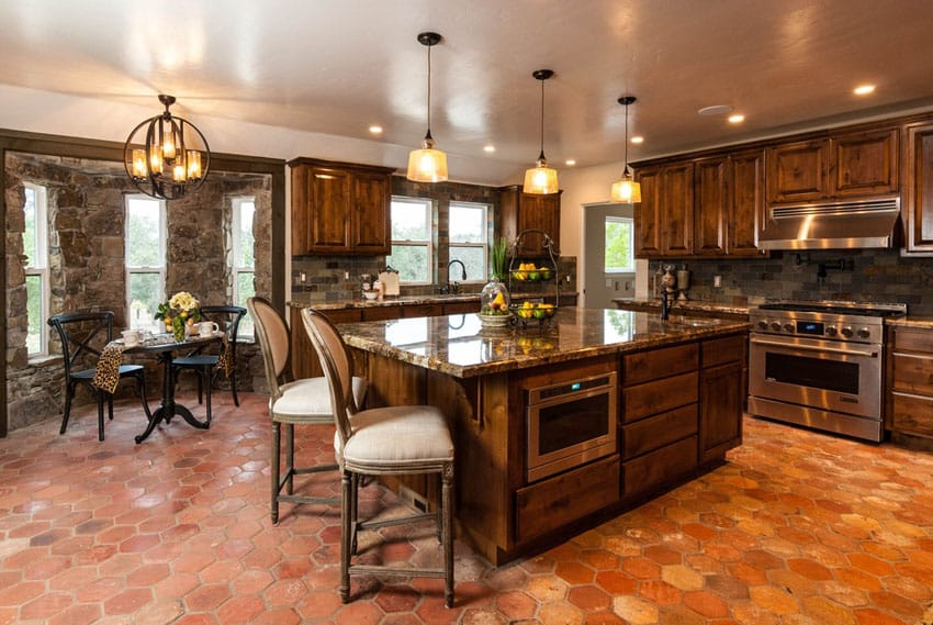Traditional kitchen with terra cotta tile floors stone walls