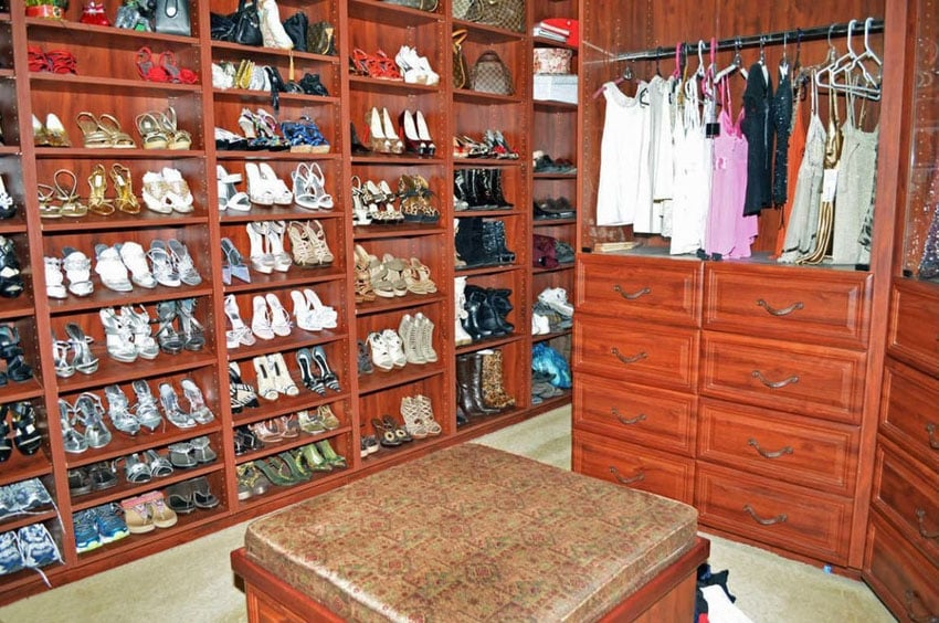 Traditional walk in closet with wall sized shoe rack center seating ottoman