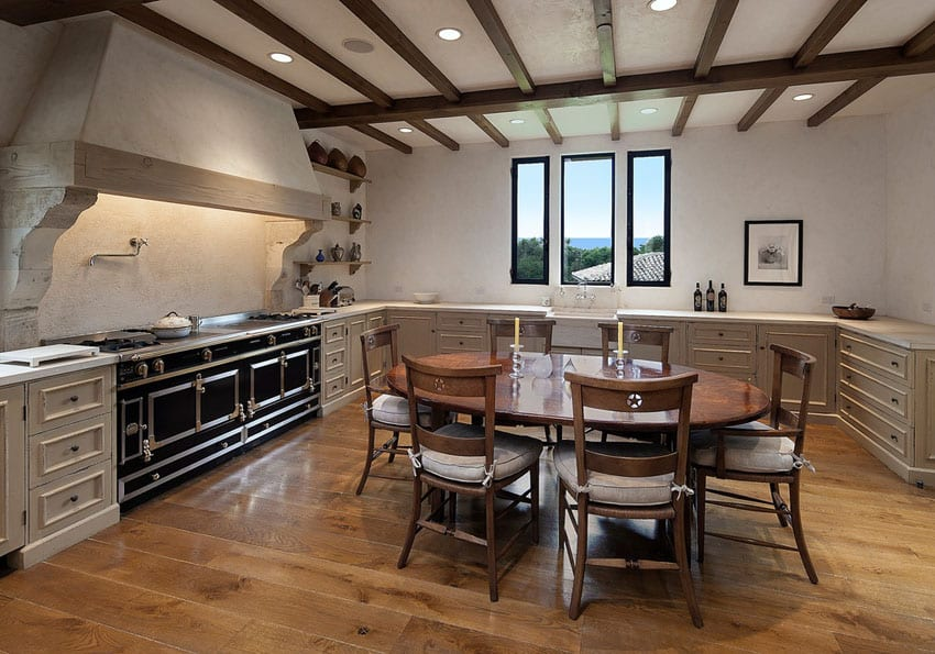 U shaped rustic kitchen with large stove and hardwood floors