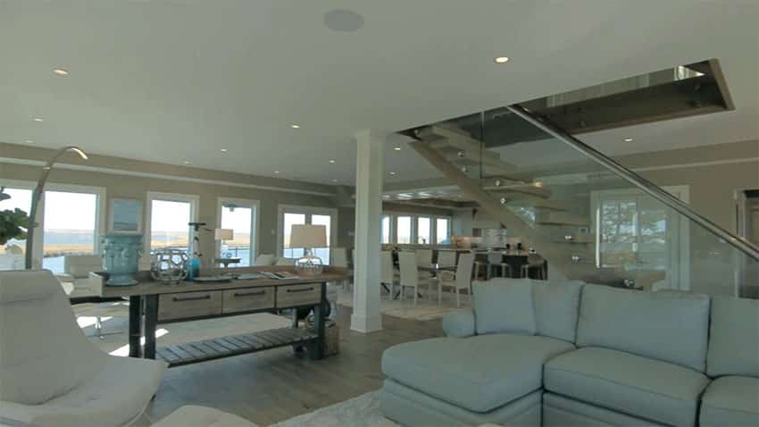 Open living room to dining area with wraparound water views