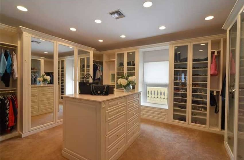 Walk in closet with custom cabinetry large mirror wardrobe