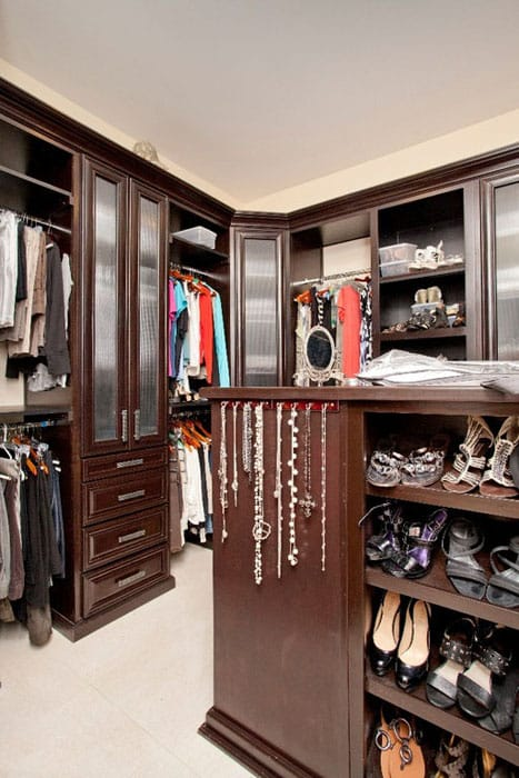 Walk in closet with dark wood cabinetry and travertine floor tiles