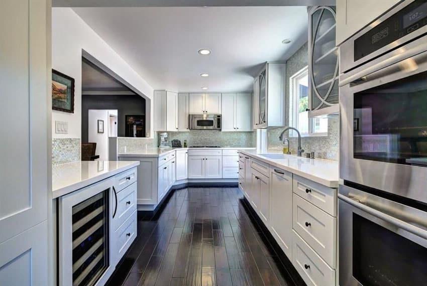 White cabinet galley kitchen with birch wood flooring