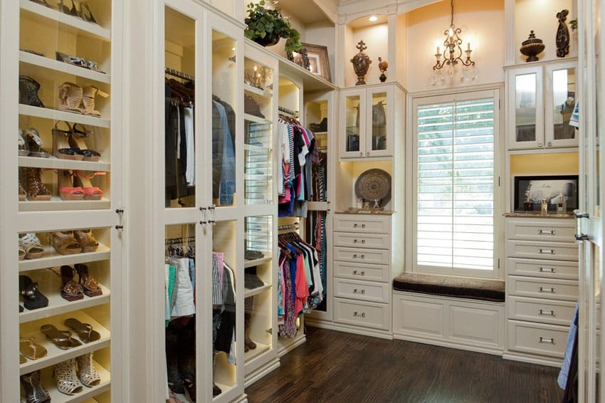 White walk in closet with hardwood floors shoe rack mirror dresser drawers and window view