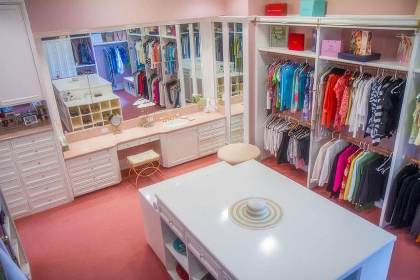 White walk in closet with quartz island and pink carpet