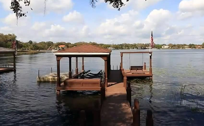 Backyard boat house on lake with wood swing