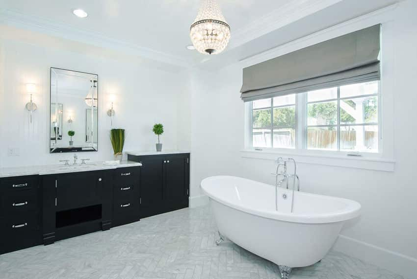 Bathroom with small chandelier and claw foot tub with silver feet
