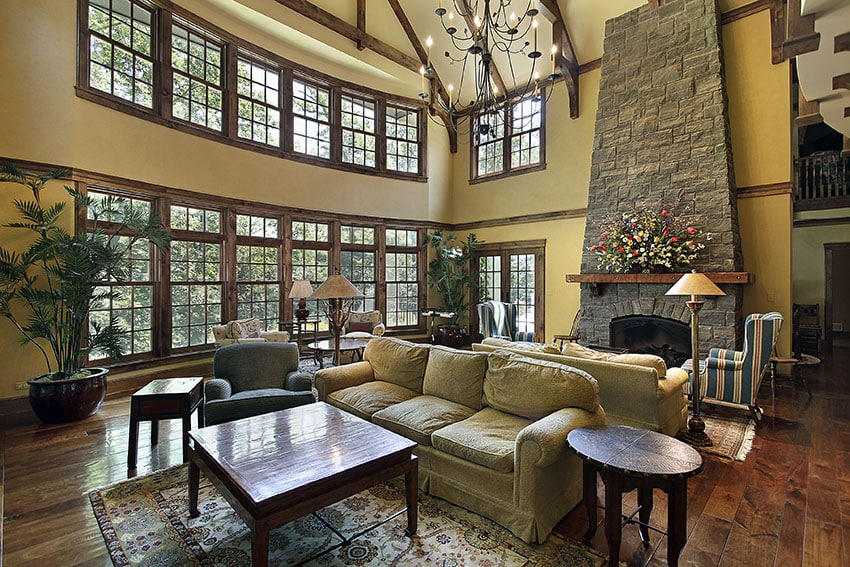 Beautiful formal living room with high angled stone fireplace wood floors and high ceiling
