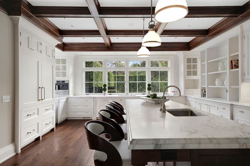 Beautiful kitchen with white cabinets white marble counters and wood coffered ceiling