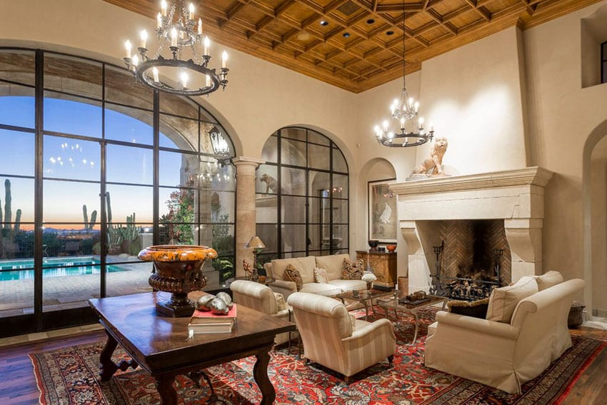 Beautiful living room with box ceiling, large stone fireplace and rustic chandeliers