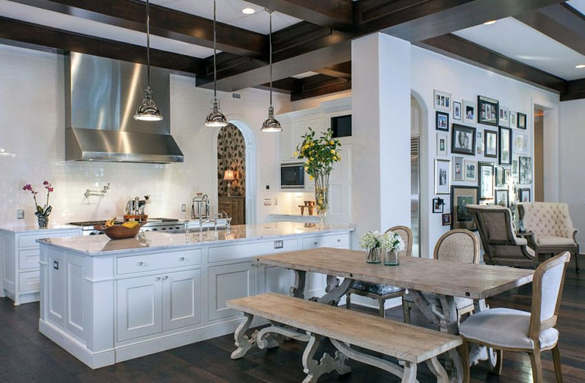Beautiful luxury kitchen with white shaker cabinetry and rustic picnic style dining table
