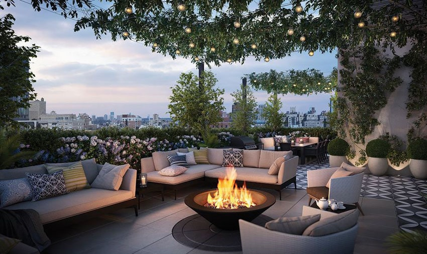 Beautiful rooftop patio area with landscaped plants, outdoor furniture, fire pit and city views