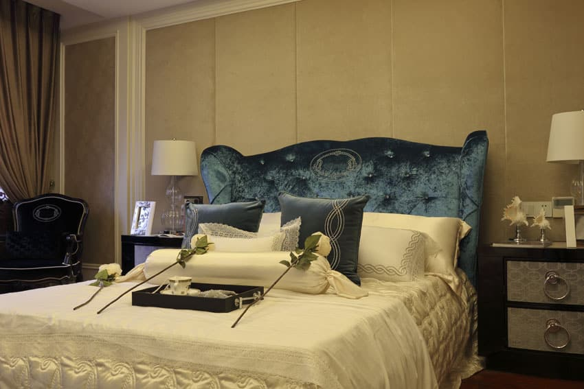Bedroom with blue fabric headboard, and matching silver front night stands