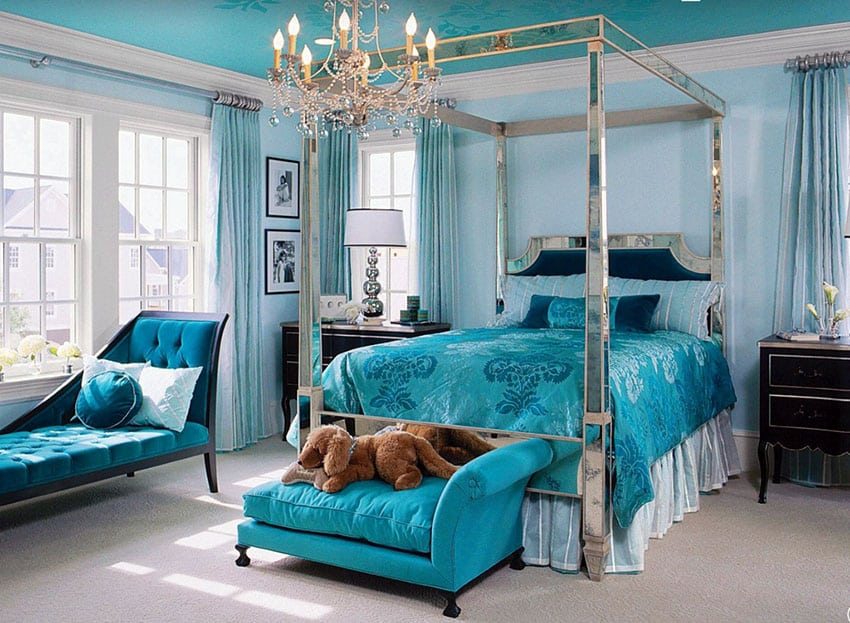 Bright blue master bedroom with mirrored four post bed, chandelier and chaise lounge by the window