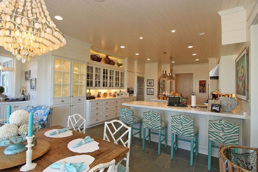 Bright beach style kitchen with marble counters, glass door cabinets and breakfast bar