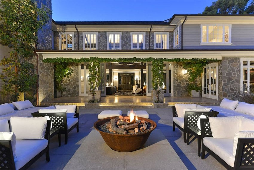 Concrete patio behind luxury estate home with stone construction