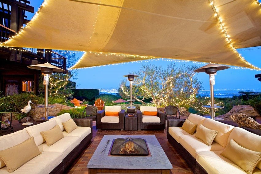 Contemporary brick patio with outdoor seating and canopy shade over fire pit