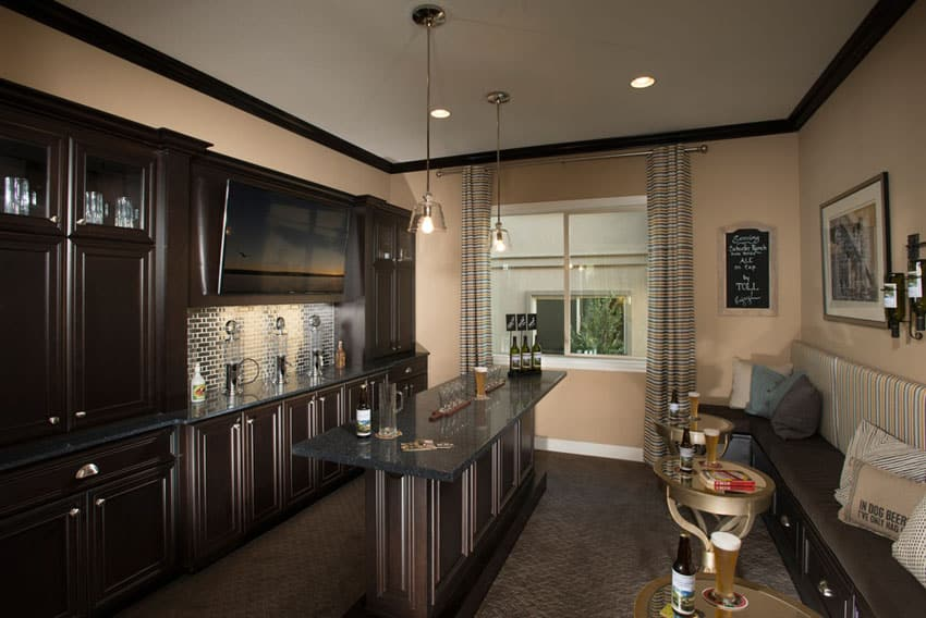Contemporary home bar with dark wood cabinets and black granite counters