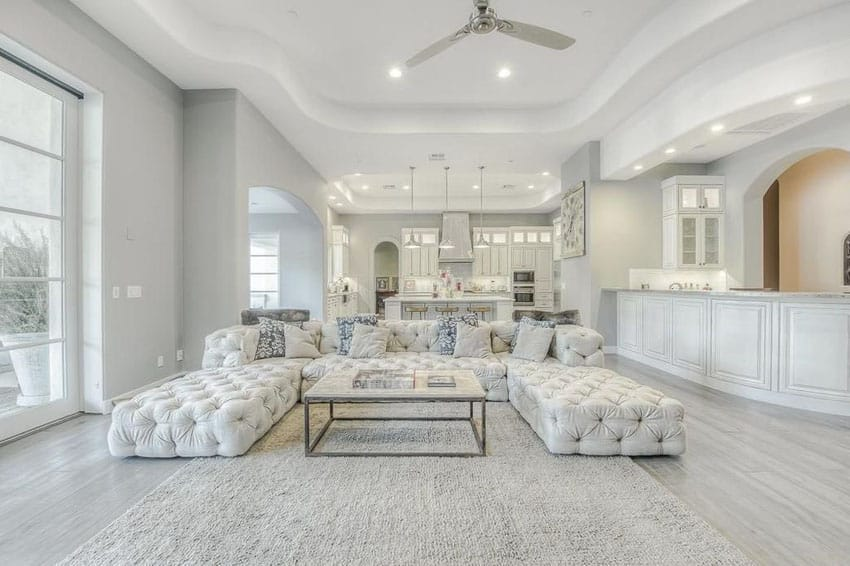 Contemporary living room with porcelain tile floors and white tufted furniture