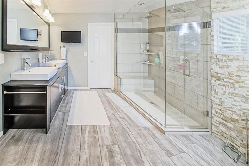 Beautiful master bathroom with frameless shower and wood grain floor tile