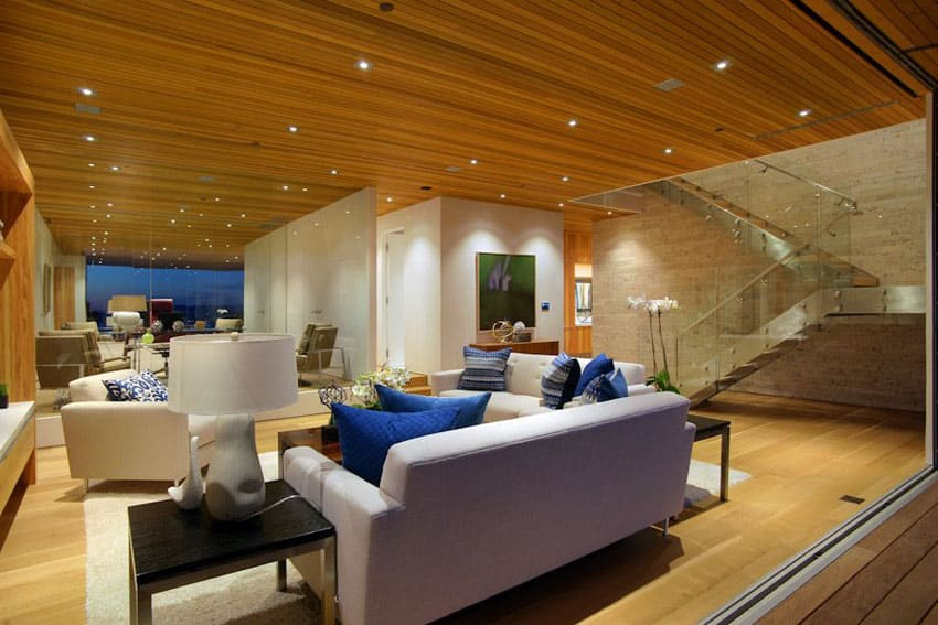 Contemporary living room design with retracting doors to patio and wood plank ceiling