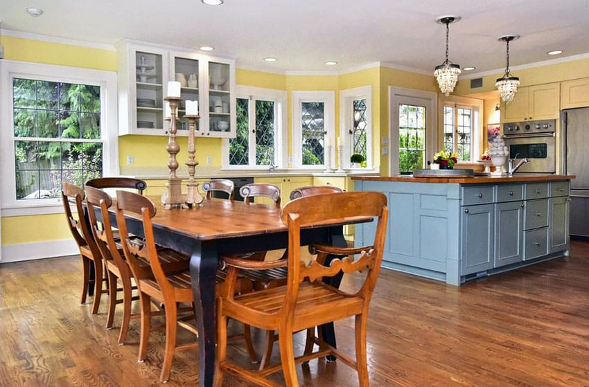 Cottage kitchen with yellow cabinets blue painted island and mini chandeliers