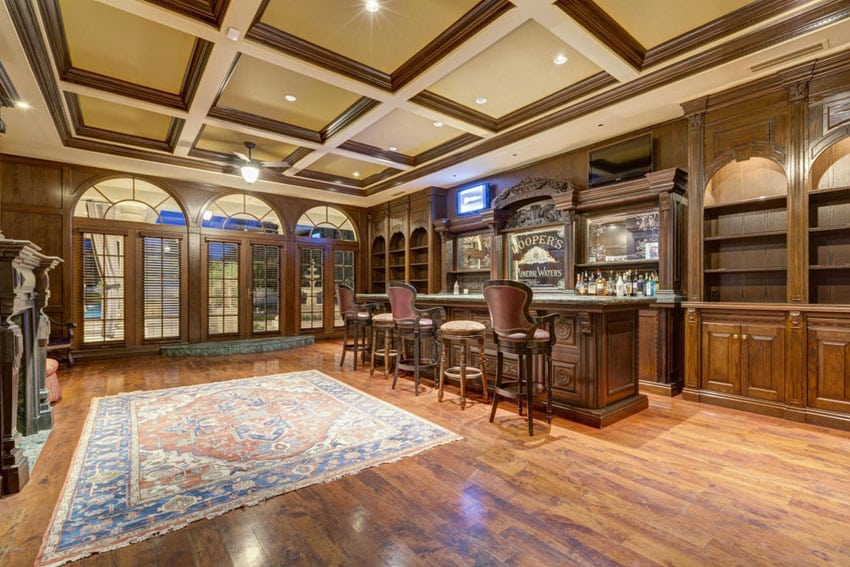 Craftsman custom home bar with decorative cabinetry and high ceilings