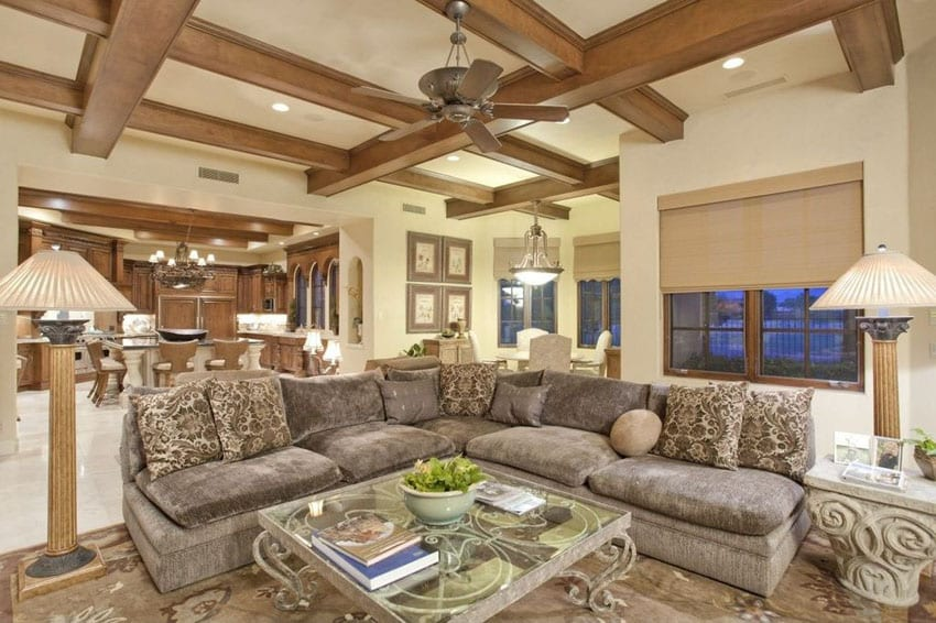 Craftsman living room with sectional couch marble flooring and wood coffered ceiling