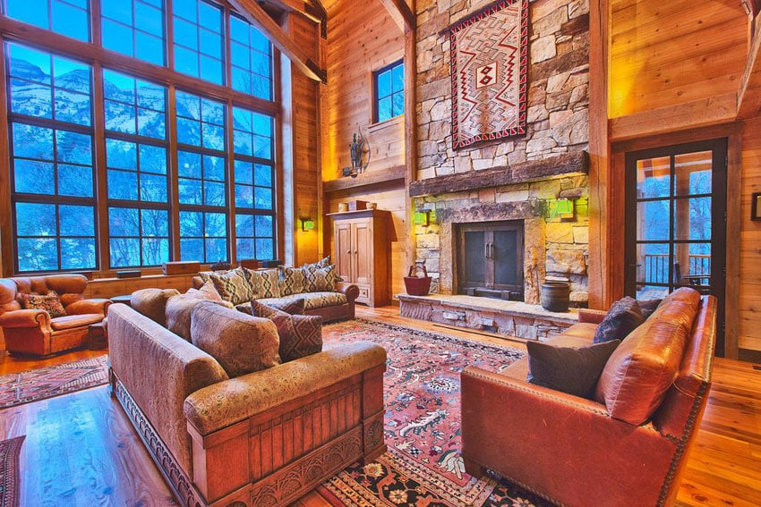 Warm craftsman living room with stone fireplace, hardwood floors, large windows and tall ceiling