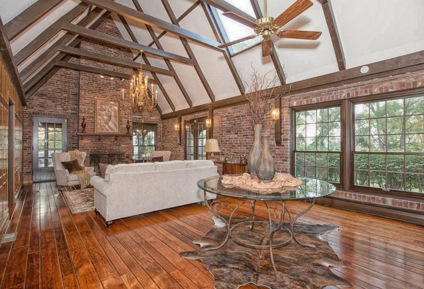 Craftsman style living room with high cathedral ceiling, brick walls, hardwood floors and fireplace