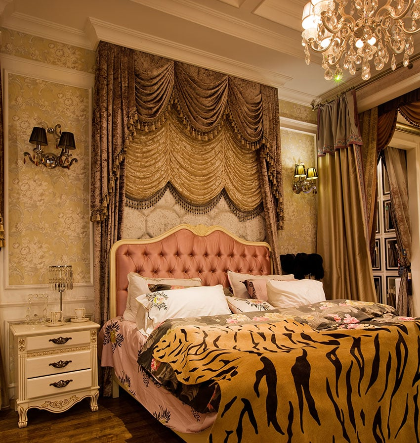 Custom designed bedroom with exotic furnishings such as bed drapery, tiger throw, and chandelier