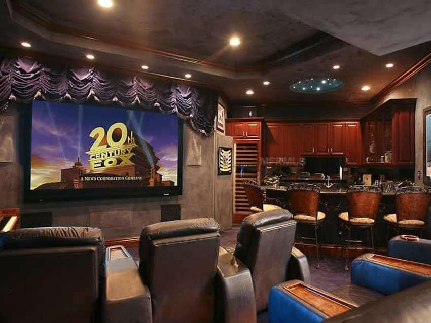 Custom home bar in movie room with comfortable seating