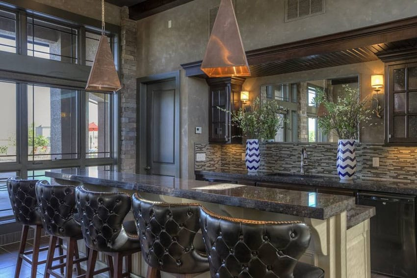 Custom home bar with leather barstools and glass backsplash