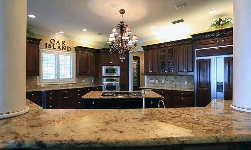 Dark wood cabinet kitchen with beige granite counters and white pillars